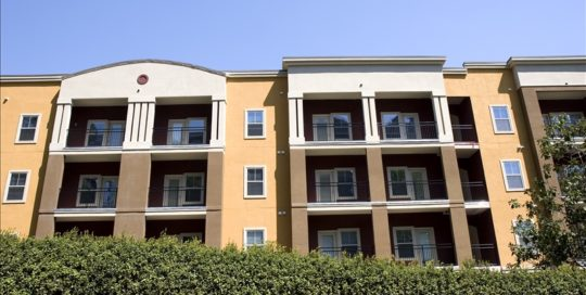 A colorful condominium complex rising over a hedge
